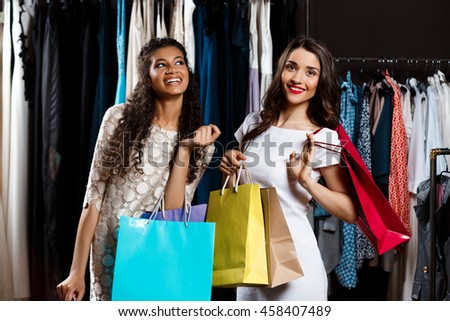 Two young beautiful girls making shopping in mall.