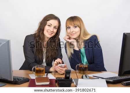 Two young beautiful girls office talking over a cup of tea - stock photo