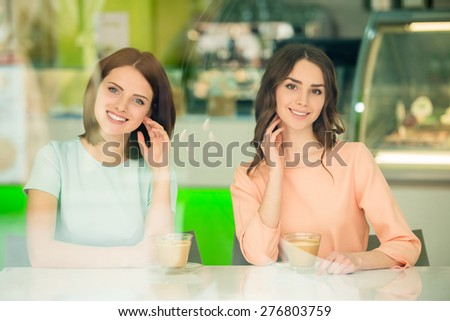 Two young beautiful girls sitting in urban cafe and drinking  coffee. - stock photo