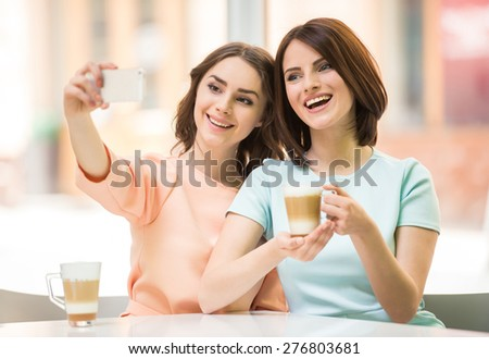 Two young beautiful girls sitting in urban cafe  and making selfie. - stock photo
