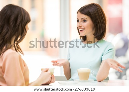 Two young beautiful girls sitting in urban cafe with coffee and talking. - stock photo