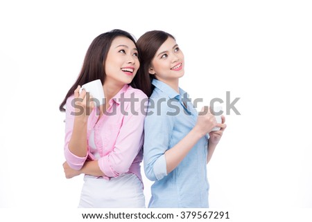 Two young beautiful girls standing back to back and drinking coffee isolated on a white background - stock photo