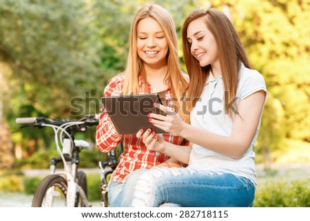 Two young beautiful happy girls sitting on a bench in a green park smiling and looking at the tablet in their hands, sport bikes standing near, selective focus - stock photo