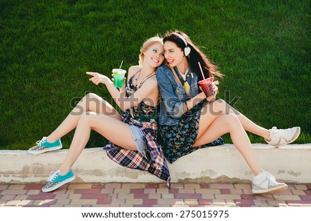 two young beautiful happy stylish hipster girls, cocktail, smoozy drink, denim, smiling, happy, fashion, cool accessories, amazed, vintage style, having fun, park, sitting, grass, pointing finger,  - stock photo