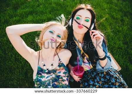 two young beautiful stylish hipster girls, friends together, cocktail, drink, denim outfit, smiling, fashion, cool accessories, vintage style, having fun, park, crazy, hair, mustache, listening music - stock photo