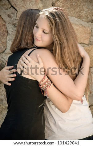 Two Young Beautiful Teen Girls friendly happy Hug against natural stone background - stock photo