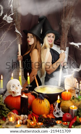 Two young beautiful witches with brooms next to the cauldron - stock photo