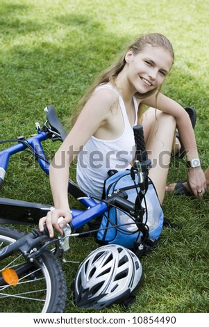 two young beautiful woman are visiting paris in summer with bicycle - stock photo