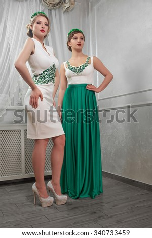 two young, beautiful woman, brunette, blonde in white short dress and long green dress, on heels, hands on hips, in the room. - stock photo