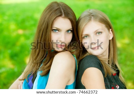 Two young beautiful  woman  on green background - stock photo