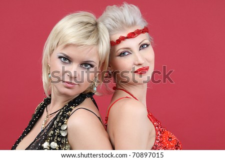Two young beautiful woman on red background