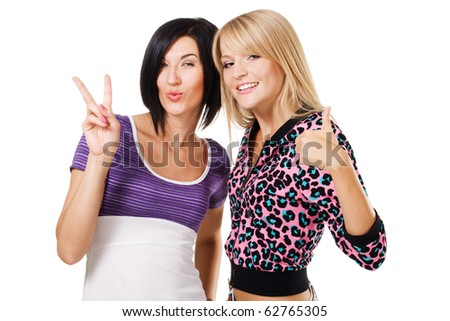 "Two young beautiful woman showing ""Thumbs up"" and ''Peace'' signs. Isolated on white background - stock photo"