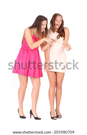 Two young beautiful woman smiling and pointing down over white background - stock photo