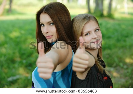"Two young beautiful women: brunette and blonde showing ""thumbs-up"" sign and smiling at summer green park."