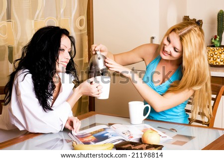 two young beautiful women drink tea in the kitchen and gossip