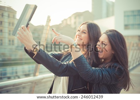 two young beautiful women friends in town using tablet - stock photo