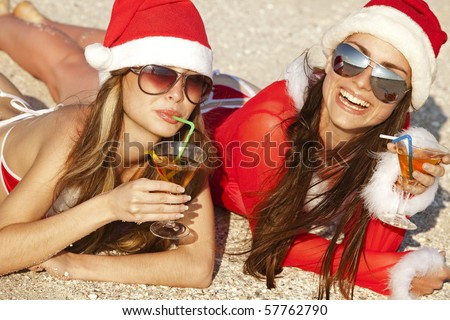 Two young beautiful women in christmas suit with martini glass on the beachfront - stock photo