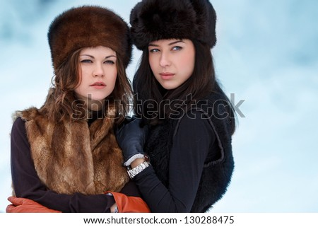 Two young beautiful women in fur hats in winter forest