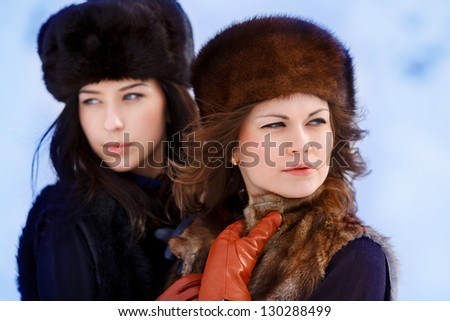 Two young beautiful women in fur hats in winter forest in focus only one
