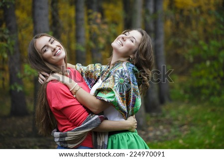 Two Young beautiful women, on yellow background autumn nature - stock photo