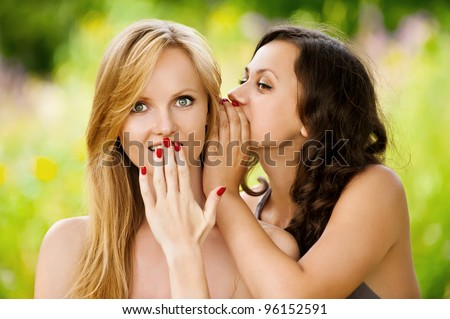 Two young beautiful women secret at summer green park - stock photo
