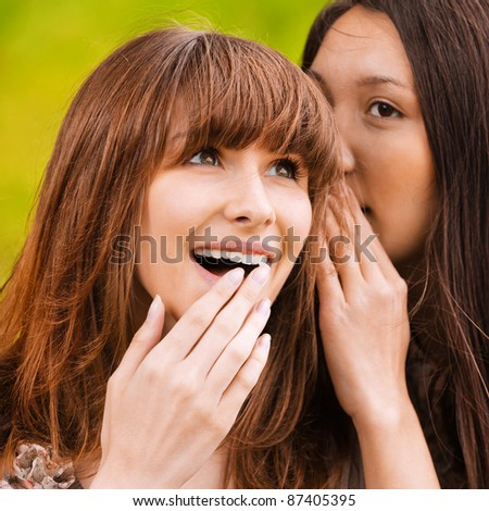 Two young beautiful women talking about something at summer green park. - stock photo