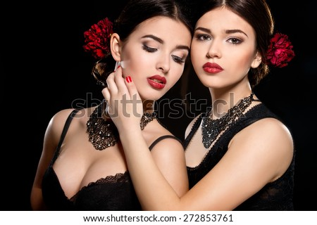 Two young beautiful women with stylish make-up and red flower in her hair. Spanish women - stock photo