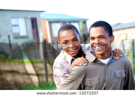 Two young black boys piggy backing one another. - stock photo