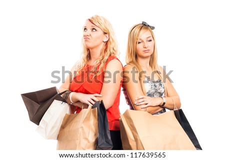 Two young blond unhappy women holding shopping bags, isolated on white background. - stock photo