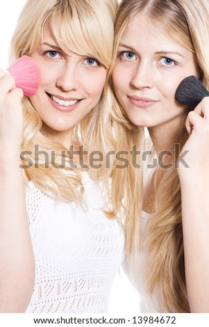 two young blond woman putting make up, studio white - stock photo