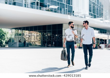 Two young blonde and black hair modern businessman, walking outdoor in the city, talking and chatting  - working, successful, business concept - stock photo
