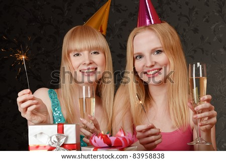 Two young blonde women celebrating birthday - stock photo