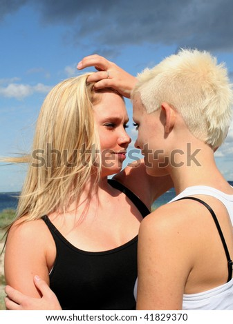 two young blonde women flirting at the beach