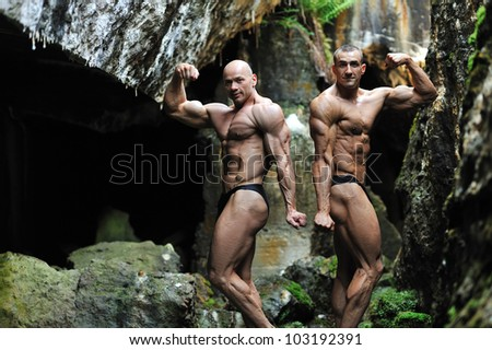 Two young bodybuilders posing in a cave