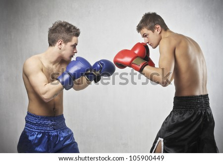 Two young boxers facing each other in a match