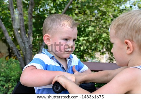 Two young boys arguing over a scooter both gripping the handlebars as they try to determine who is going to ride it next - stock photo