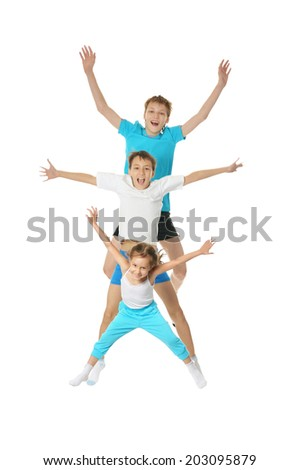 Two young boys brothers and little sister exercising isolated on white background - stock photo