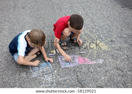 two young boys drawing with sidewalk chalk - family and kids - stock photo