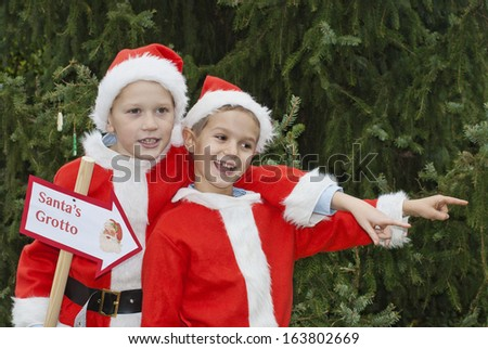 Two young boys dressed as Santa holding a sign and pointing to Santa's Grotto - stock photo