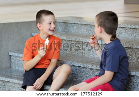 Two young boys eating ice cream and making fun - stock photo