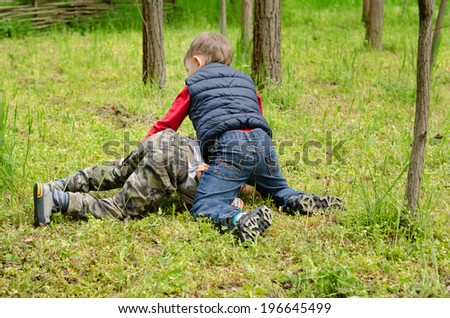 Two young boys fighting on the ground with one on top of the other holding him down on the grass