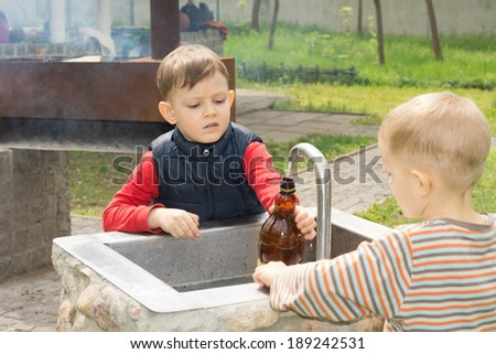 Two young boys filling a bottle of water from a running tap over a stone sink at a campsite - stock photo