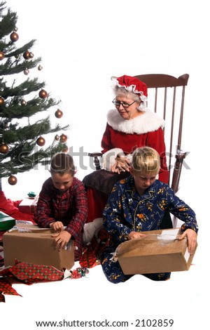 Two young boys gathered around the Christmas Tree opening their gifts while Mrs. Santa Claus sits watching from  her rocking chair.