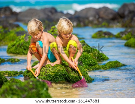 Two young boys having fun on tropical beach, happy best friends playing with fishing nets, friendship concept - stock photo
