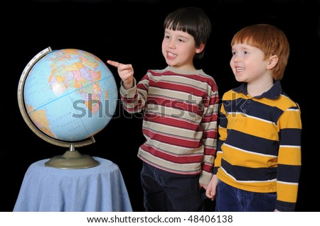 Two young boys identify various countries on the globe - stock photo