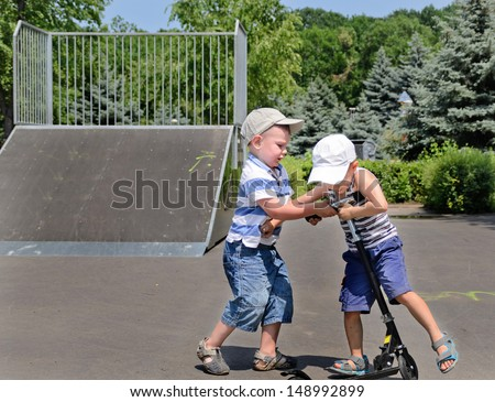 Two young boys in baseball caps fighting over a scooter in a skate park as the one bullies the other to get off - stock photo