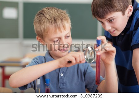 Two young boys in science class at school examining the contents of a test tube through a magnifying glass with happy smiles - stock photo
