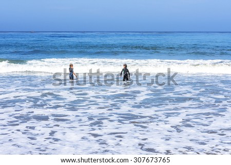 Two young boys in wet suits playing in the surf on a sandy beach with sea foam along the rugged Big Sur coastline, near Cambria, CA. on the California Central Coast. - stock photo