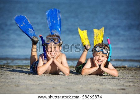 two young boys laying on a beach with snorkeling gear on - stock photo