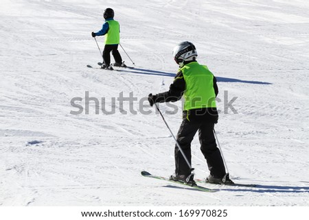 Two young boys learning how to ski and wearing green vests. - stock photo